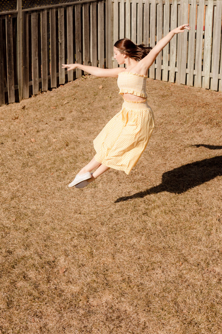 Emily Gilmore—Girl in yellow dress dancing in backyard