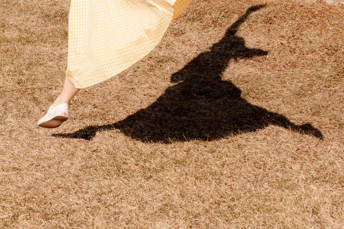 Emily Gilmore—Girl in yellow dress walking in backyard