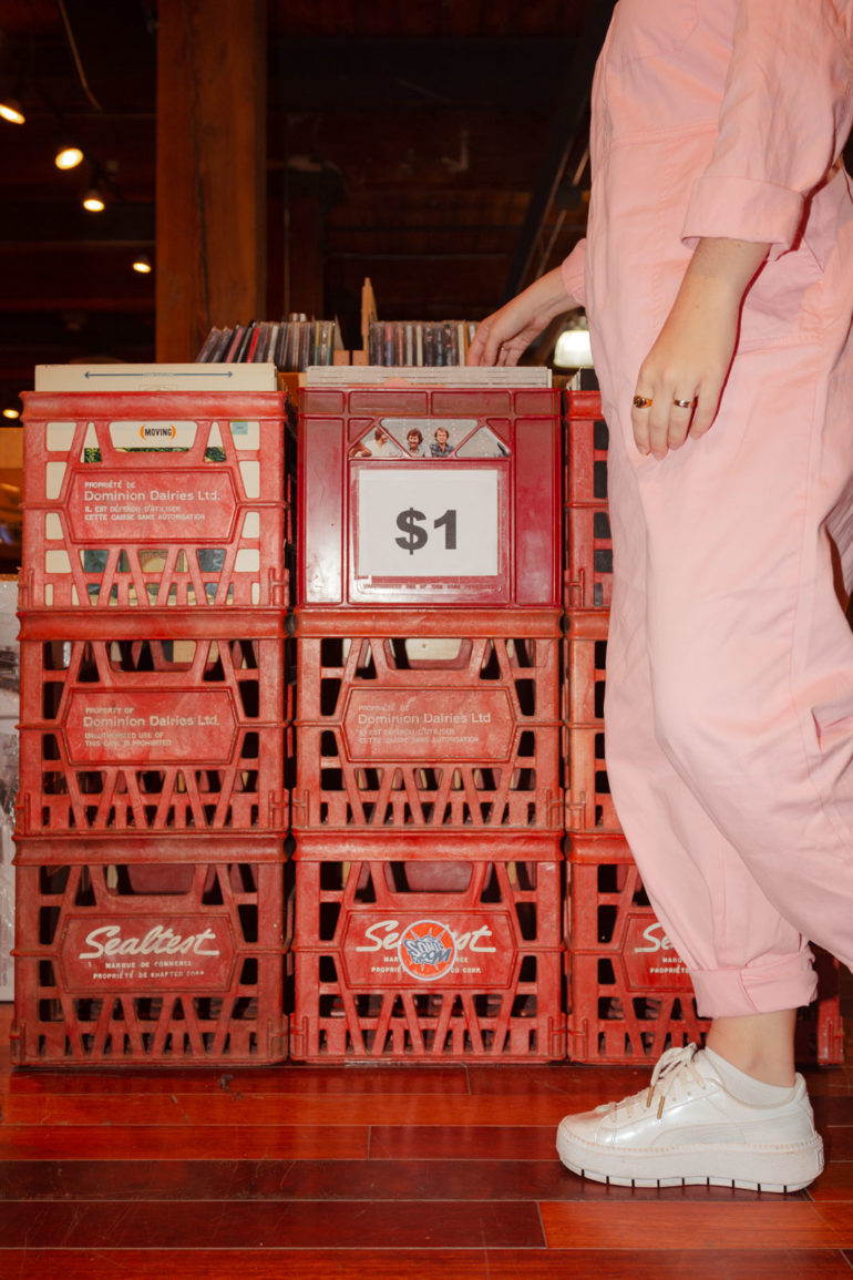 Girl in pink standing in front of milk crates full of Vinyl Albums