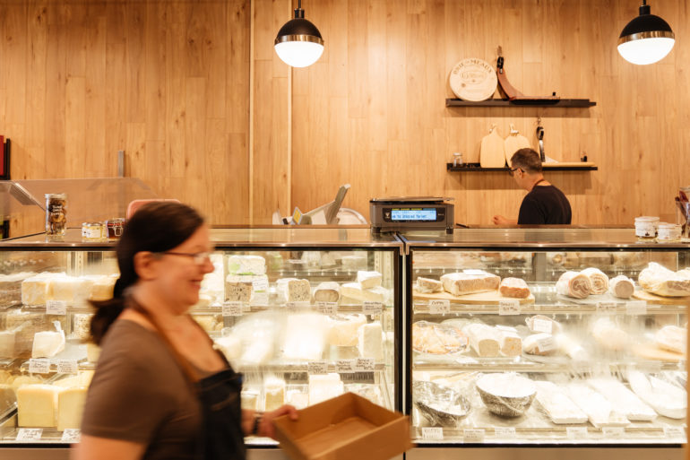 woman walking past Deli counter at theUnboxed Market