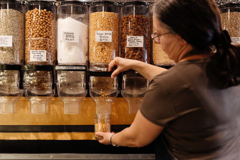 woman filling container with grain at theUnboxed Market