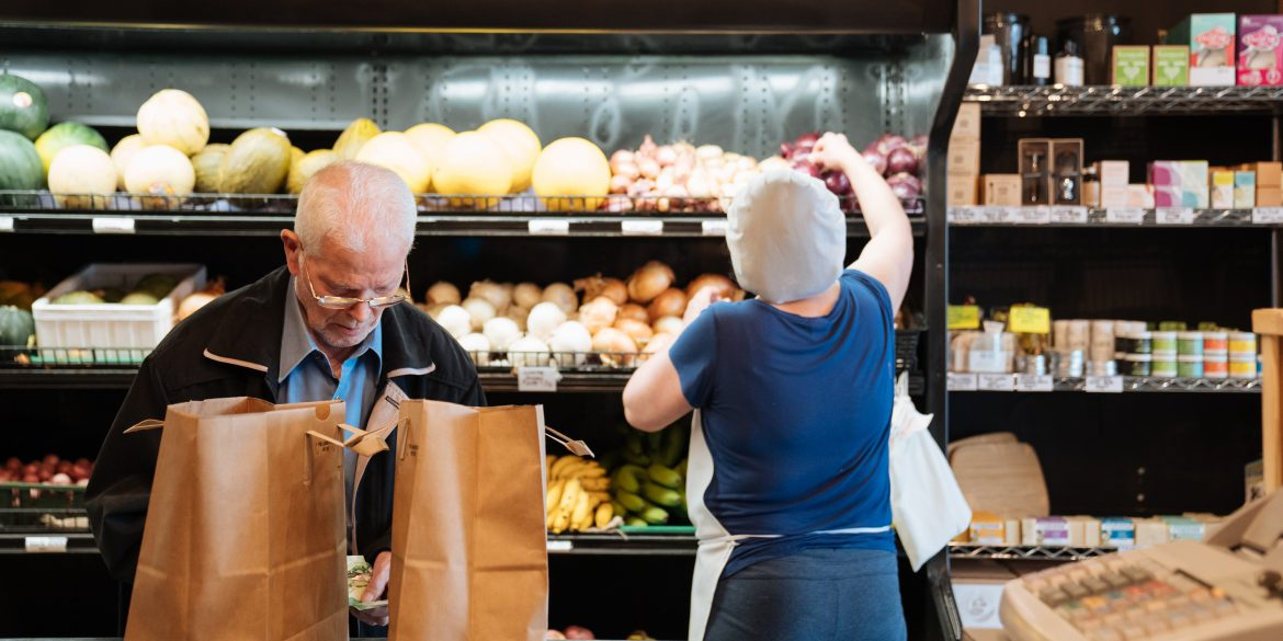 Customer with paper bags paying for groceries at the Unboxed Market